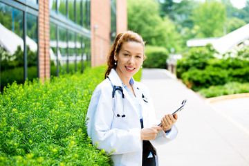 Female health care professional, outside on hospital campus