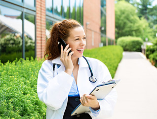 Portrait smiling female doctor on phone outdoors hospital campus