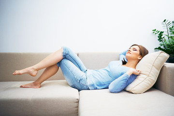Relaxing young woman sofa lying.