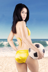 Beautiful woman in bikini holding ball 2