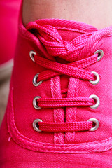 Closeup of vibrant pink sneakers shoes boots on female feet