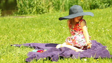 Girl child kid in straw hat relaxing on the meadow