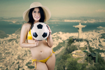 Cheerful woman holding ball in Brazil 1