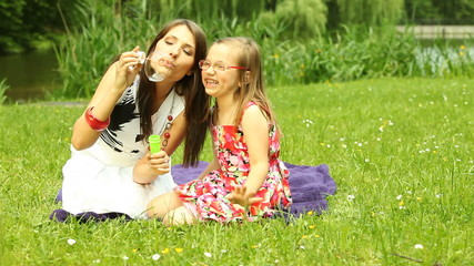 Mother with little daughter blowing a soap bubbles outdoor