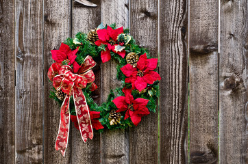 Christmas flower wreath on rustic wooden fence