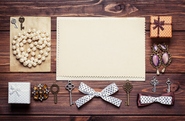 old paper sheets surrounded by retro objects on wooden backgroun