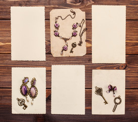 old paper sheets and retro jewelry on wooden background