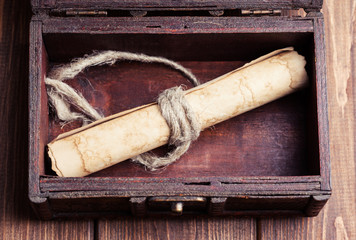 old paper roll inside treasure chest on wooden background