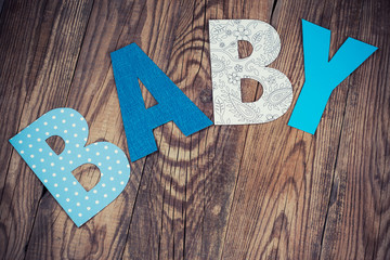 letters of word baby on wooden background