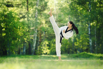 Karate girl makes high kick on forest outdoor location