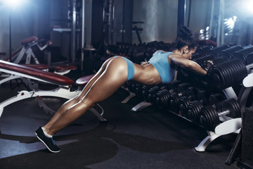 brunette fitness woman doing push up in the gym