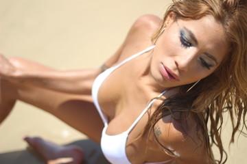 Beautiful woman with a white bikini posing sexy at the beach