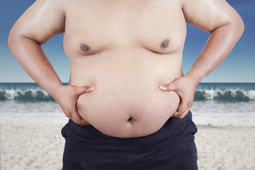 Fat man holding his stomach at beach