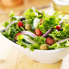 bowl of leafy green salad with olives, tomatoes and cucumber.
