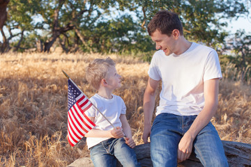 handsome father and his little son holding american flag celebra