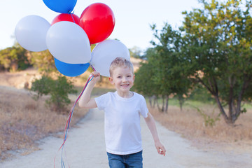 running cheerful boy holding colorful balloons and celebrating 4