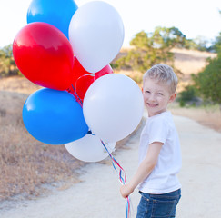 little cheerful boy holding colorful balloons and celebrating 4t