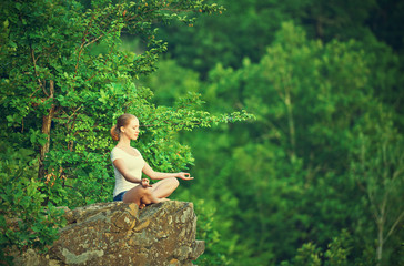 woman meditating in lotus posture, doing yoga on top of the moun
