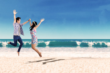 Happy asian couple jumping at beach