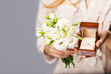 close up of bride with bouquet of flowers and wedding ring.