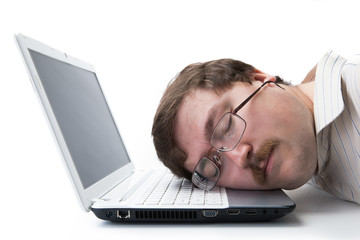 man sleeping on a notebook keyboard at the workplace