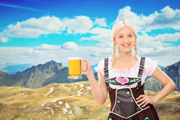 Bavarian woman holding a beer high in the mountains