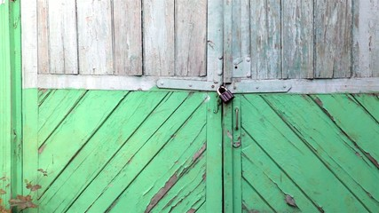 Green wooden gate with a lock