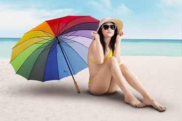 Sexy model with colorfull umbrella at beach