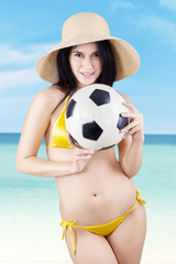 Sexy woman holding a soccer ball at beach