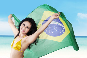 Sexy woman holding brazilian flag on seaside