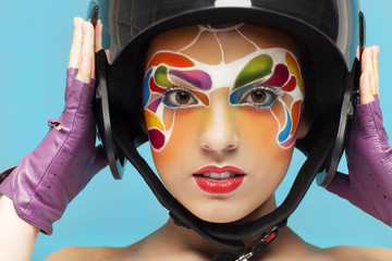 Young model with bright creative make up with helmet