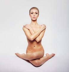 Nude woman performing yoga asana