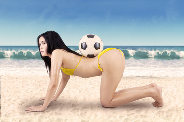 Sexy woman with soccer ball on vacation