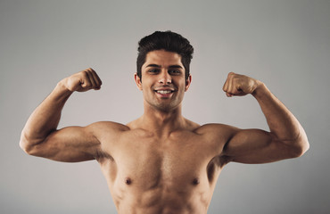 Muscular man pulling his biceps to show off