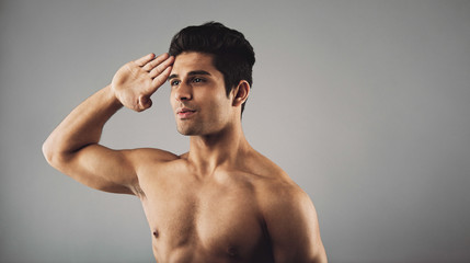 Young muscular man saluting