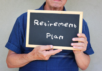 senior man holding blackboard with the phrase pension plan writt