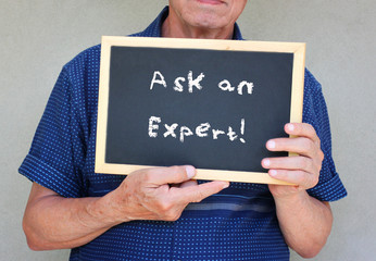 close up of senior man holding blackboard with the phrase ask an