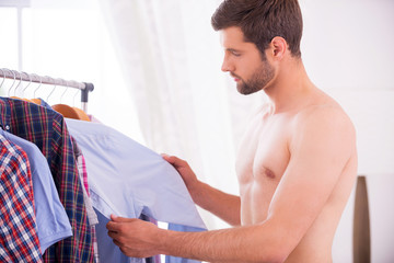Choosing shirt to wear.