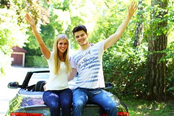 junges Paar sitzt auf einem Cabrio
