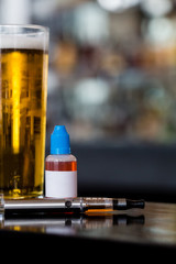 Glass of beer, e-liquid and e-cig