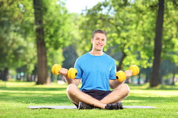 Man working out in park seated on grass