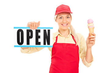 Female ice cream vendor holding an open sign