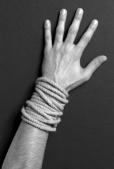 Hand with rope and black background