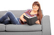 Beautiful girl lying on a couch and reading book