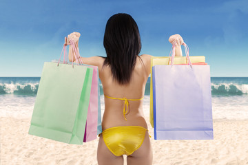 Woman holding shopping bag at beach 1