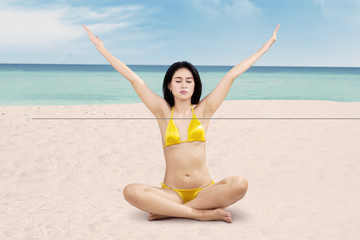 Woman is meditating at tranquil beach