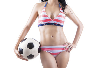 Woman wearing striped swimsuit holding ball