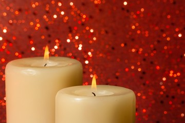candles with flame on red bokeh
