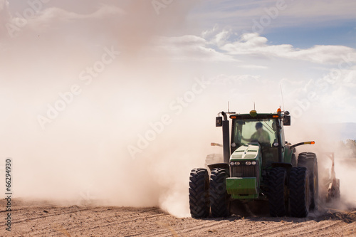 Tractor in a dusty dry farm - 66294930
