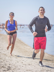 happy people running on the beach